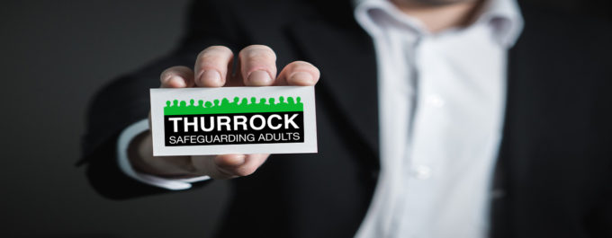 Image of someone holding the Thurrock Safeguarding Adults Board logo