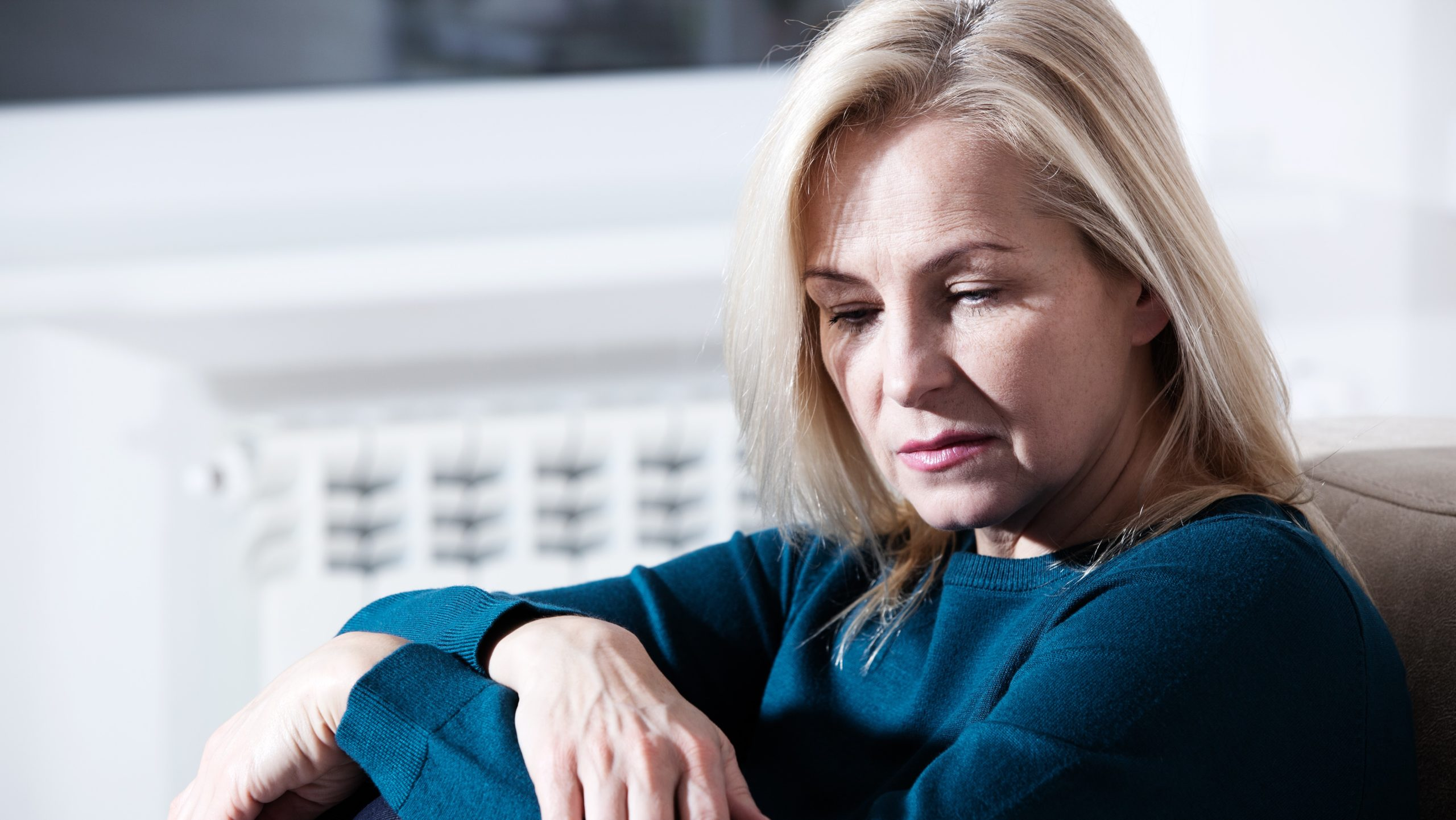 Middle aged woman barefoot sitting on the couch, hugging her head, at home. The concept of sadness and loneliness.