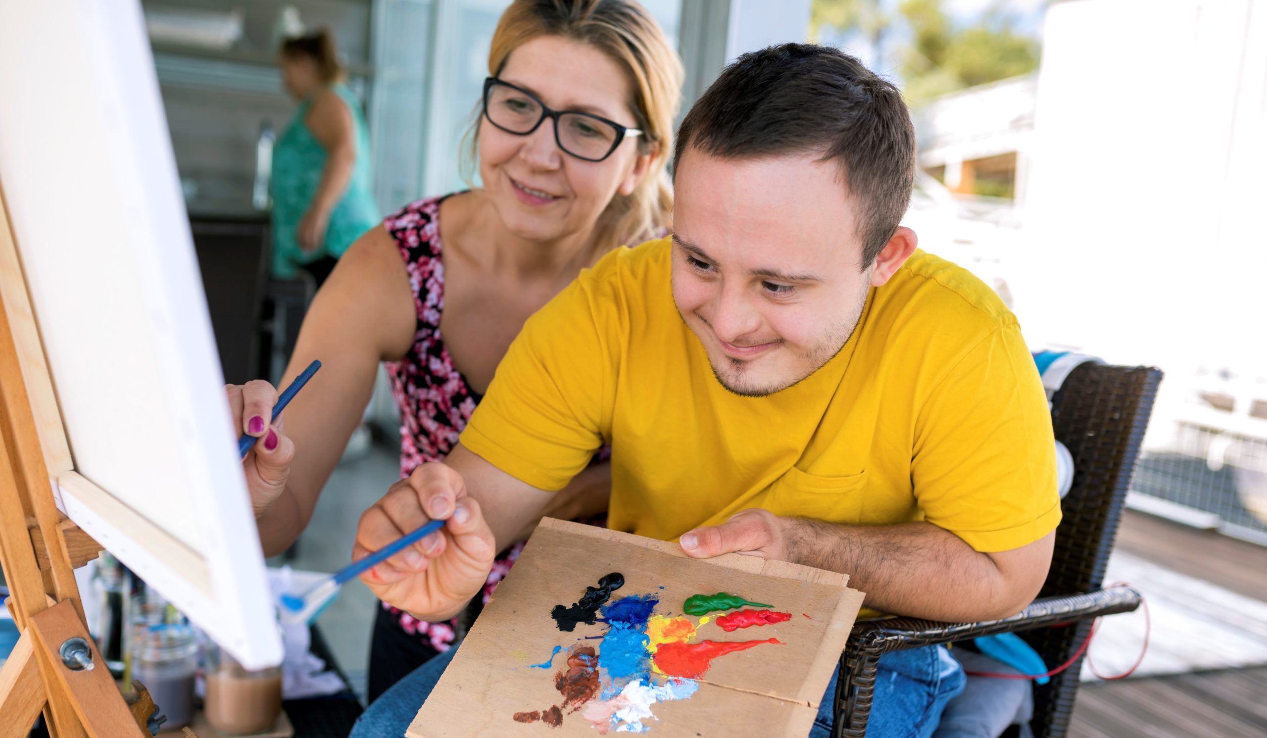 Male with Down syndrome painting on canvas with someone